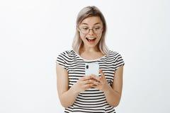 Ww, ce nouvel APP est si facile à utiliser Amie attirante stupéfaite avec les cheveux justes dans les verres ronds et le T-shirt  Image libre de droits