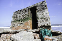 WW2 coastal defence fortification. WWII beach defence uncovered by tidal surge erosion on the UK coastline. This concrete WW2 military coastal fortification stock photos