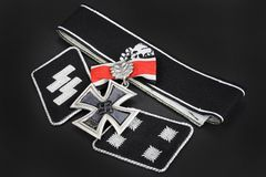 WW2 German Waffen-SS military insignia with Iron Cross award. On black background Stock Images