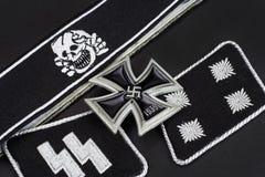 WW2 German Waffen-SS military insignia with Iron Cross award. On black background Stock Photos
