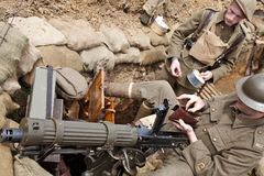 WW1 trench. BELTRING, UK - JULY 19: Re-enactors in British Army WW1 uniform clean an authentic Vickers machine gun whilst posing in replica trench systems at the Royalty Free Stock Photo