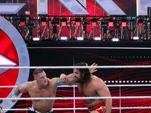 WWE摔跤手由投掷拳打决定的约翰・希南风在Rusevduring wr 免版税库存照片