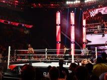 WWE-brottaren Seth Rollins skriker på folkmassan som den Roman Reigns stirrandet Arkivbilder