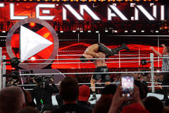 WWE Champion Brock Lesner sets up to F-5 Seth Rollins by placing Royalty Free Stock Photos