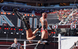 WWE Wrestler Randy Orton backflips Seth Rollins off the top turn Royalty Free Stock Image