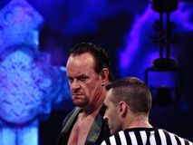 WWE Wrestler the Undertaker stares across ring with ref standing. SANTA CLARA - MARCH 29: WWE Wrestler the Undertaker stares across ring with ref standing next Royalty Free Stock Image