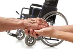 Wwheelchair. Hands Of An Elderly Man Holding The Hand Of A Woman Royalty Free Stock Photos