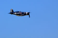 WWII Corsair. WWII era F4U Corsair figher plane flying against a clear blue sky at an airshow in Rochester, NY royalty free stock image