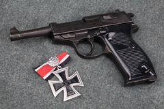 WWII era nazi german army 9 mm semi-automatic pistol with Iron Cross award. On grey uniform background royalty free stock photography