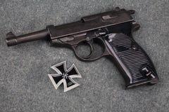 WWII era nazi german army 9 mm semi-automatic pistol with Iron Cross award. On grey uniform background royalty free stock photo