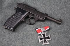 WWII era nazi german army 9 mm semi-automatic pistol with Iron Cross award. On grey uniform background royalty free stock images