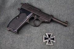 WWII era nazi german army 9 mm semi-automatic pistol with Iron Cross award. On grey uniform background royalty free stock image