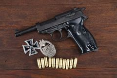 WWII era nazi german army Walther P38 handgun and military awards - Iron Cross and Tank assault badge. On wooden table stock photo