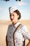 WWII Nurse portrait. A beautiful young WWII nurse, in authentic uniform, stares off into the dry dusty landscape. close up head and shoulders. Uniform is the royalty free stock photos