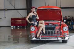 WWII Pinup Model And Muscle Car. A pinup model posing with a 1950s car royalty free stock images