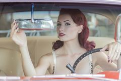WWII Pinup Model And Muscle Car. A pinup model posing with a 1950s car stock images
