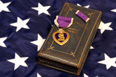 WWII Purple Heart on American Flag. Vintage WWII Purple Heart on presentation case resting on top of the American flag royalty free stock photography