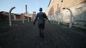 Slow motion. Rear view of a young German soldier with a rifle running in the middle of the path outside the. WWII reenactment. Back view of a young handsome stock footage