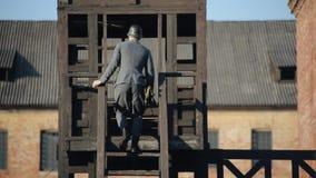 WWII-reenactment En ung tysk ordningsvakt som klättrar trappan av en träwatchtower på territoriet av en död stock video