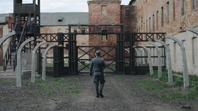 A back close-up of a male actor dressed in a German soldier uniform looking at a death camp reconstruction. Turning over. WWII reenactment. A rear half-body view stock video