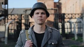 A portrait of a young German soldier walking towards the camera. A blurred view of a death camp reconstruction on the. WWII reenactment. Slow motion. A close stock video footage