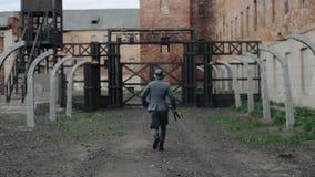 WWII-reenactment Tillbaka sikt av en ung stilig tysk soldat med ett gevär som kör till portarna av ett dödläger arkivfilmer