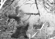 WWII Soldier Firing M1 Rifle Through Smoke Stock Photography