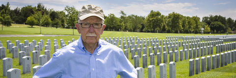 WWII veteran at military cemetery. WWII veteran among the headstones at a military cemetery stock photo