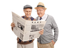 Wwo senior gentlemen reading a newspaper Royalty Free Stock Image
