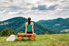Wwoman, das auf einer Bank in den Hügeln sitzt stockfoto
