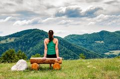 Wwoman sitting on a bench in the hills stock photo