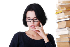Wwomen in eyeglasses by stack of books. Royalty Free Stock Photos