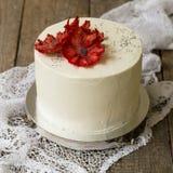与红色菠萝鸦片花的美丽的白色罂粟籽蛋糕 在的白蛋糕wwooden与鞋带织品的背景 图库摄影