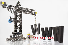 WWW with crane and worker. Black wooden W alphabetic letters being set up by construction crane and worker symbolizing Website under construction Stock Photography
