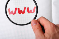 WWW search - Searching internet concept. WWW - world wide web word on paper under magnifying glass. Searching internet concept royalty free stock image