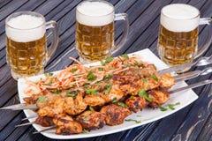 Wyśmienicie piec na grillu jagnięcy skewers z piwem na stole obraz stock