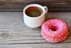 Wyśmienicie słodki świeży różowy filiżanka kawy na starym drewnianym tle i pączek Śniadanie, fast food, piekarni pojęcie zdjęcie stock