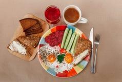 Wyśmienicie śniadanie od jajek, chleb z masłem, kiełbasa na Colorfull talerzu Kawa, Czerwony sok z Białymi kwiatami Nóż i lud Obrazy Stock