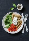 Wyśmienicie śniadanio-lunch lub - krepy z uwędzonym łososiem, szpinakami i kwaśną śmietanką na ciemnym tle, obrazy stock