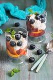 Wyśmienicie żywienioniowy deser z curd kremowymi czarnymi jagodami brzoskwinią i, kropić z cukieru proszkiem i dekorować z nowymi zdjęcie royalty free