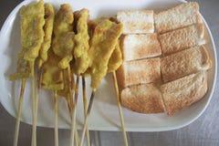 Wyśmienicie Azjatycka kuchnia świniowaty Satay z grzanką na talerzu zdjęcia stock