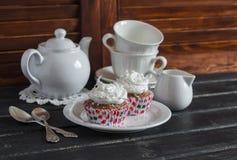 Wyśmienicie babeczki i herbata ustawiająca na drewnianym stole handluje porcelany świeżego porcelanowe truskawek herbatę razem Fotografia Stock