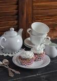 Wyśmienicie babeczki i herbata ustawiająca na drewnianym stole handluje porcelany świeżego porcelanowe truskawek herbatę razem Obrazy Stock