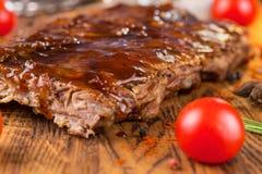 Wyśmienicie barbecued ziobro przyprawiali z korzennym fastrygowanie kumberlandem na starej nieociosanej drewnianej ciapanie desce obrazy royalty free