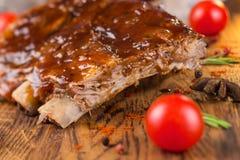Wyśmienicie barbecued ziobro przyprawiali z korzennym fastrygowanie kumberlandem na starej nieociosanej drewnianej ciapanie desce obrazy stock