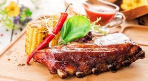 Wyśmienicie barbecued ziobro przyprawiali z korzennym fastrygowanie kumberlandem, słuzyć z sałatką i piec na grillu kukurudzy na  fotografia royalty free