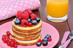 Wyśmienicie bliny z świeżymi jagodami w różowią talerza i soku pomarańczowego zdjęcie stock