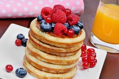 Wyśmienicie bliny z jagodami w soku pomarańczowym na stole i talerzu obraz royalty free