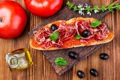 Wyśmienicie chlebowa grzanka z naturalnym pomidorem, ekstra dziewiczym oliwa z oliwek, Iberyjskim baleronem, czarnymi oliwkami i  obraz stock