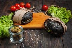 Wyśmienicie czarni hamburgery w rzemiośle tapetują na tnącej desce ciemny drewno stół Fotografia Royalty Free
